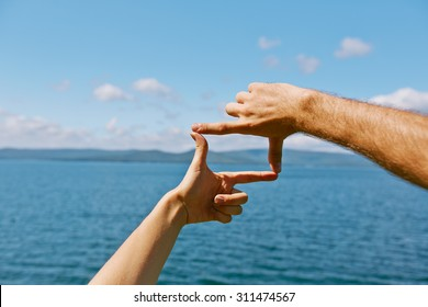 Human hands making frame against sea and skyline