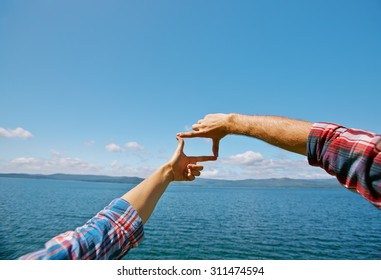 Human hands making frame against blue sky by the seaside