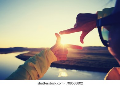 Human hands making a frame sign over sunset sky