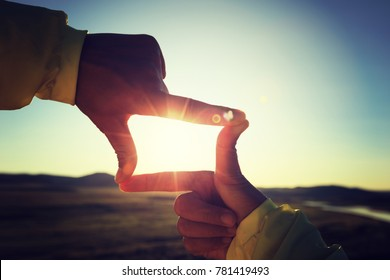 Human hands making a frame sign over sunset sky
