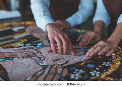 Human hands with mosaic in workshop