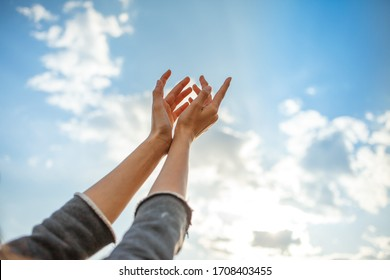 Human hands open palm up on sky background. Horizontal photo.