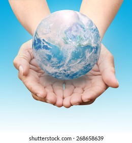 Human hands palm up with NASA global image as design element over blue shade