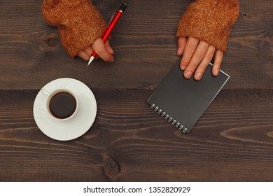 Human hands with a pen and notebook at a wooden table with a cup of coffee
