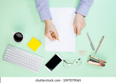 Human hands with pencil writing on paper on color table background