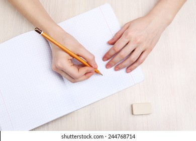 Human hands with pencil writing on paper and erase rubber on wooden table background