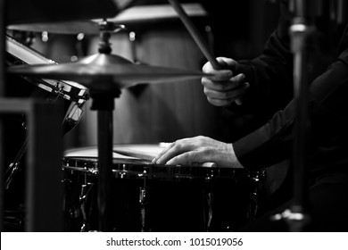 Human hands playing the drum kit in black and white