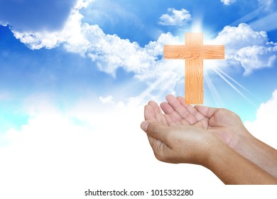 Human hands pray with cross