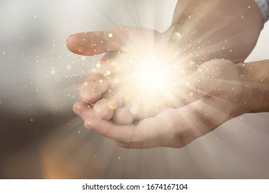 Human hands praying for blessing with lights shining
