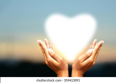 Human hands protect the heart Sky background