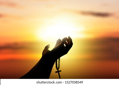 Human hands with rosary beads raised while praying to god with a sunset sky background