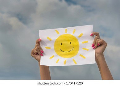fe70bedd22f human hands with sheet of paper with sun image against overcast sky -  positive thinking concept