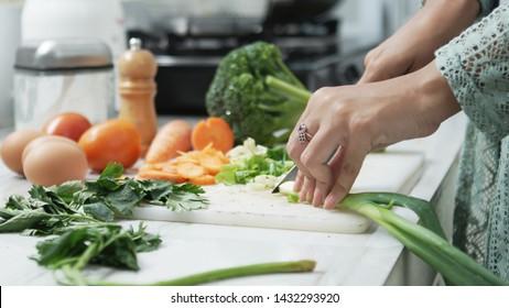 Human hands slicing vegetables in kitchen. Healthy food. Woman preparing vegetables