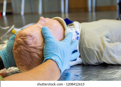 Human hands stabilisations the neck from a medical training puppet for ambulance man