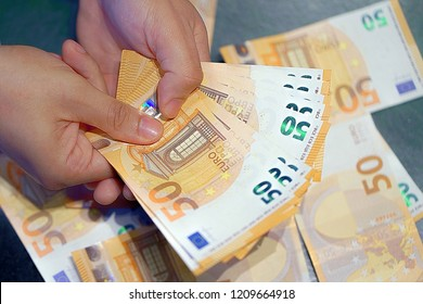 Human hands that consider 50-euro bills. In the hands of a lot of money, 50 denominations of euros