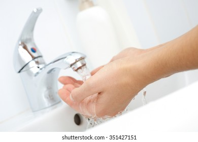 Human hands under stream of pure water from tap