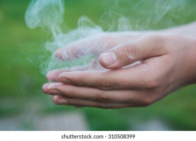 Human hands in white smoke