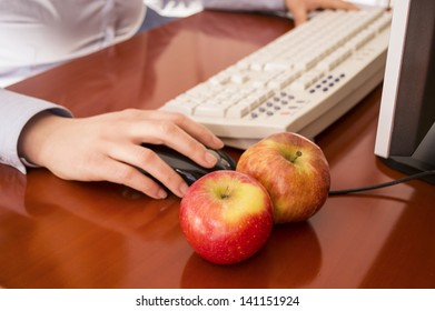 Human hands working on a computer  and two apples to eat
