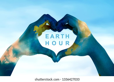 Human hands with world map skin make a heart shape with earth hour text over blue sky background. Earth hour concept