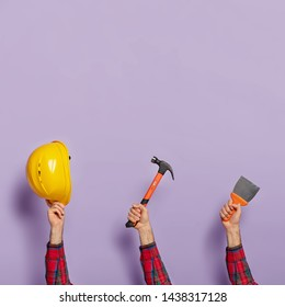 Human hands with yellow hardhat, hammer and brush for house repair. Collection of various equipment or tools for construction. Handyman poses with different things. Labour Day. Close up shot