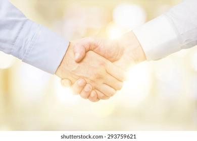 human handshake on a blurred yellow background