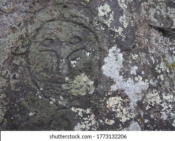 Human head petroglyph symbol carved on rock Stone wall with moss, Russian far East