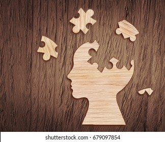 Human head silhouette with a jigsaw piece cut out on the wooden background, mental health symbol