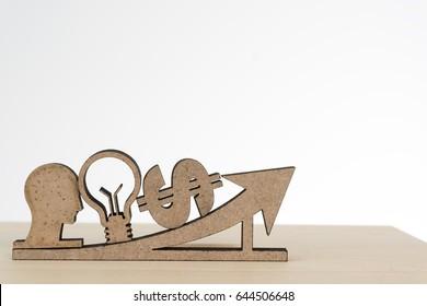 Human head,lamp idea,money and arrow sign on wood table,business success concept