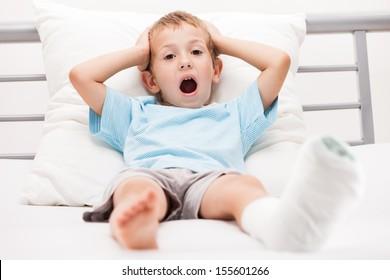 Human healthcare and medicine concept - little child boy with plaster bandage on leg heel fracture or broken foot bone
