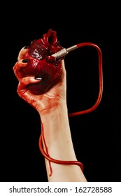 Human heart in hand with pipe, red cable isolated on black