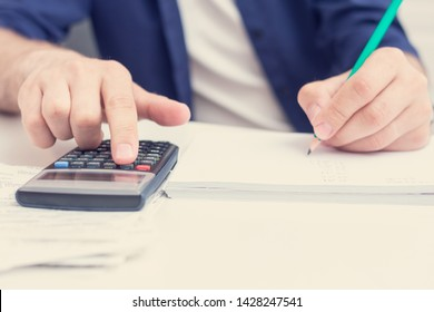 Human holding bills in her hands, man calculating family budget, calculator on the desktop, men's hands, cropped image, close up, toned