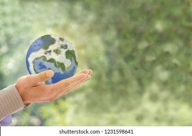 Human holding Earth in hands against green spring background and sun ray. Ecology concept,