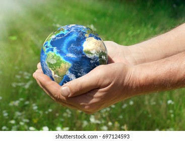 Human holding Earth in hands against green background and sun rays. Ecology concept, earth day. Elements of this image furnished by NASA