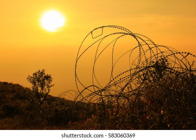 Human last stand, line of defense from enemies. Metal fences on the waste land during sunset in the orange theme