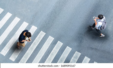 Human life in Social distance. Aerial top view with blur man with smartphone walking converse of other people at pedestrian crosswalk on grey pavement street road with empty space.