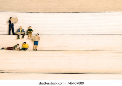 Human miniatures, mini figures of people reading standing on books. Concept background for education, culture, business and knowledge.
