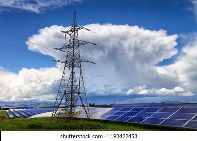 Human and nature energy. Field with solar panels and high voltage power lines with big thunderstorm on the background.
