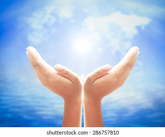 Human open empty hands with palms up over blurred world map of clouds and beautiful nature background.
