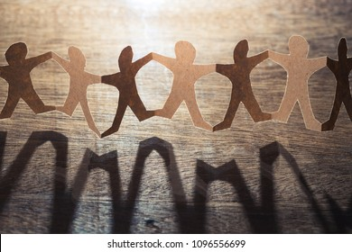 Human paper chain dolls against the light on wood background