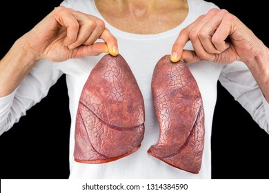 Human person holds two lung models in front of white chest isolated on black background