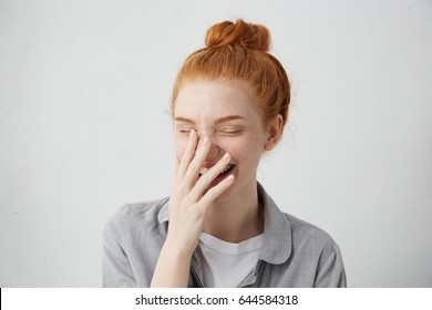 Human positive emotions and feelings. Headshot of cute timid attractive young European female with hair knot laughing from bottom of her heart, covering open mouth with hand and closing eyes