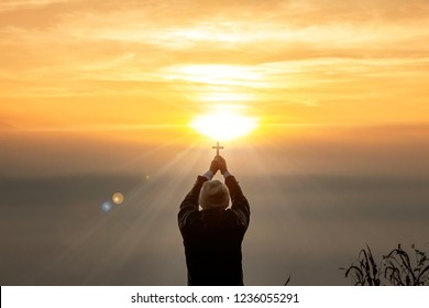 human praying to the GOD while holding a crucifix symbol with bright sunbeam on the sky