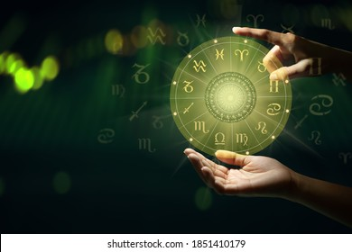 Human predicts the future. Zodiac sign wheel of fortune hologram with mandala inside. Deep green and life graph background. Copy space.