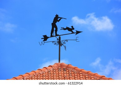 Human and rabbit Weathervane on the roof in blue sky