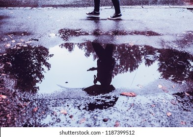 Human Reflection in water puddle on the street in rainy day.Man with umbrella walking on wet city ground