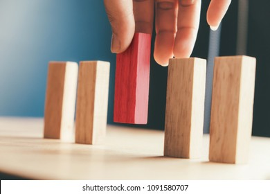 Human resource and Business concept in choose idea person from many candidate and different. Close up hand pick one of red wood block from many wood block in row.