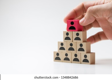 Human resource management concept by hand putting wood cube block leader on top pyramid.