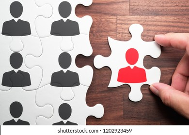 Human resource management. Personnel, employment and recruitment concept.Selecting person for the job. Assembling jigsaw puzzle on wood desk.