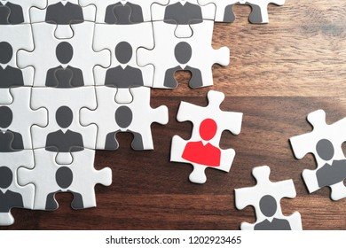 Human resource management. Selecting business person for organization.Personnel, employment and recruitment concept. Assembling jigsaw puzzle on wood desk.