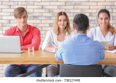 Human resources commission interviewing man at table